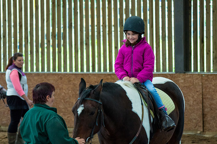 Young girl in pink riding a brown and white horse