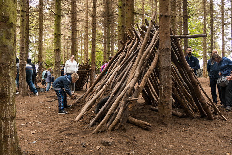 group of children and their families building a wooden tipi