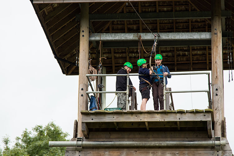 3 boys at the top of a zip-wire