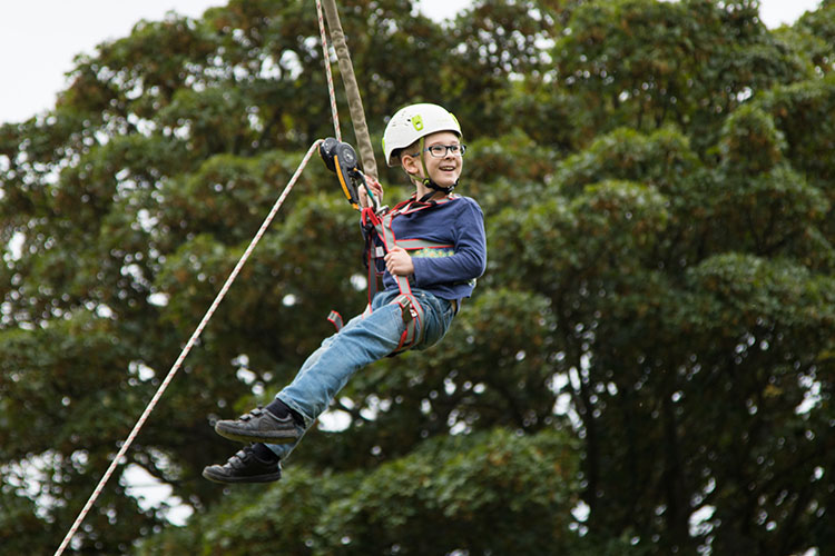 A young boy enjoying sliding down a zip-wire