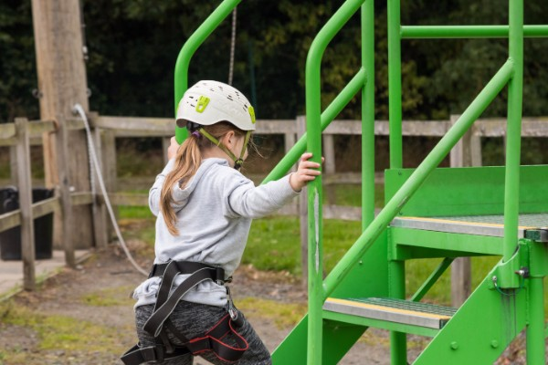A young girl climbing up some green stairs