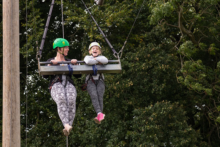 A girl and her family sliding down a zip-line