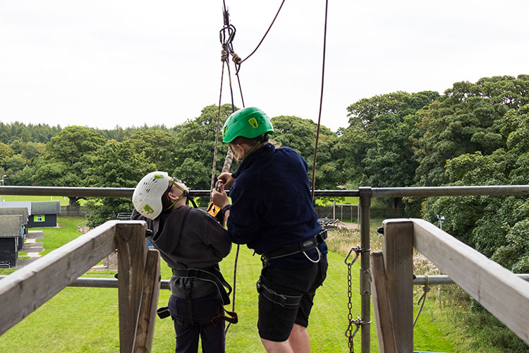 A child and her guide getting ready to slide down the zip wire