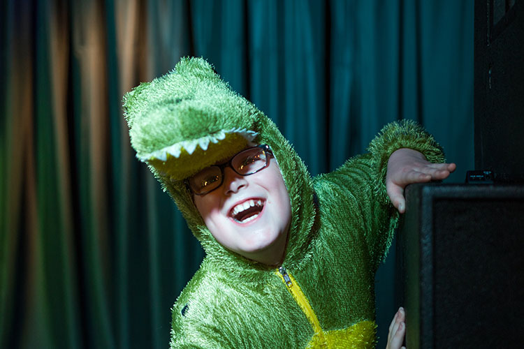 Young boy wearing a crocodile costume